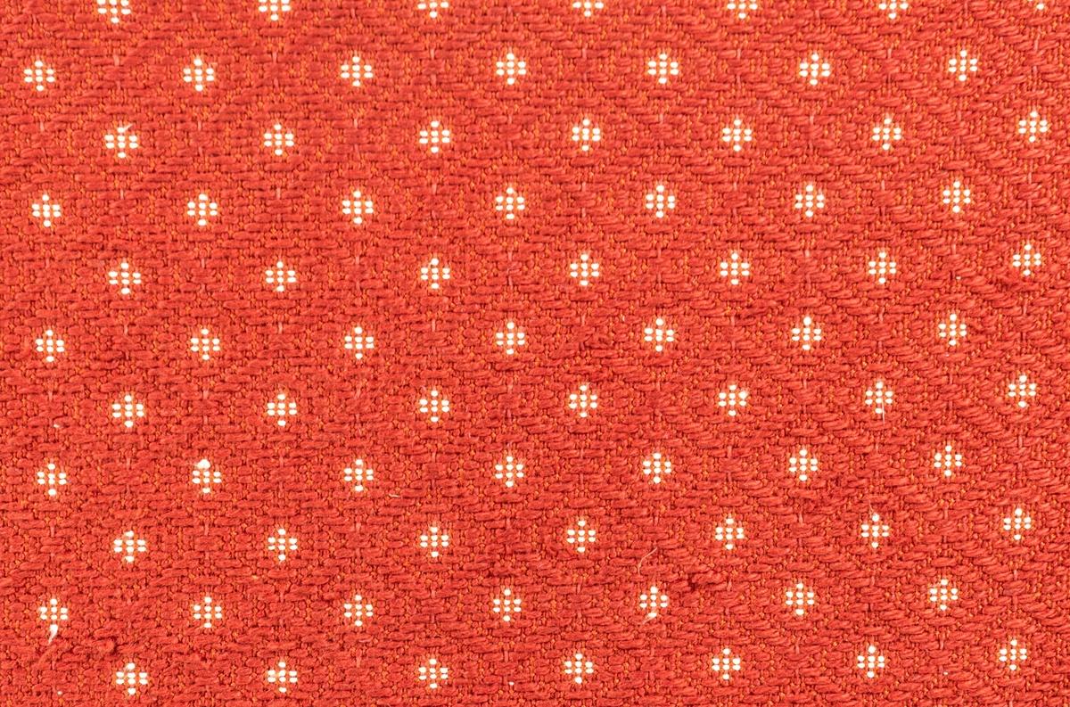 Katalogkort: Fåtölj. Ljust träslag i armstöd och ben. Sits och ryggstöd klädda med mönstervävt tyg. Varp: röd. Inslag: rett, vitt. Gåsögonliknande mönster. Sitsens kant, kantad med snodd i rött och vitt. På stolsryggens framsida fanns ursprungligen 3 textilklädda knappar, varav en saknas.  h 80cm, b 66cm, dj 77cm