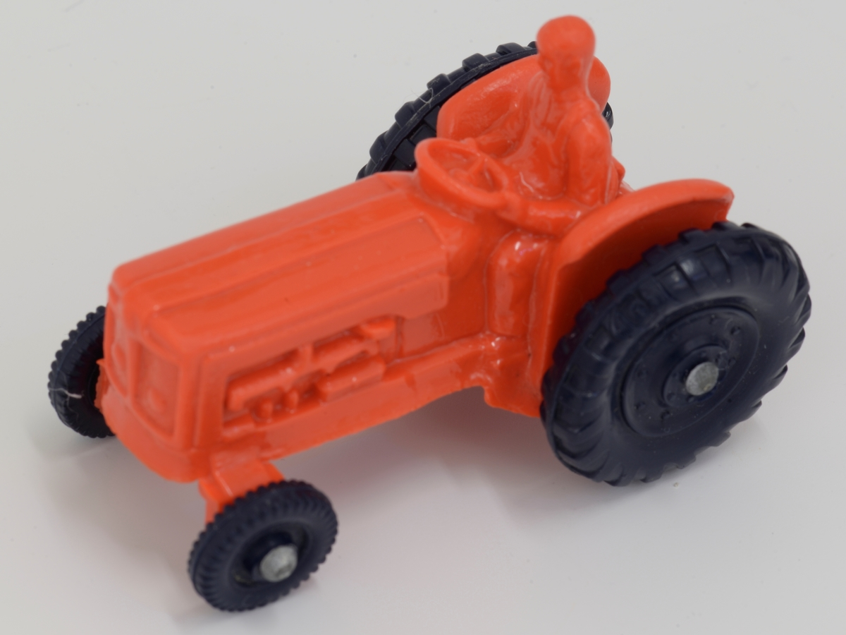 Leketraktor i rød, myk plast. Støpt i ett stykke med fører. Sorte hjul Metall hjulnav
