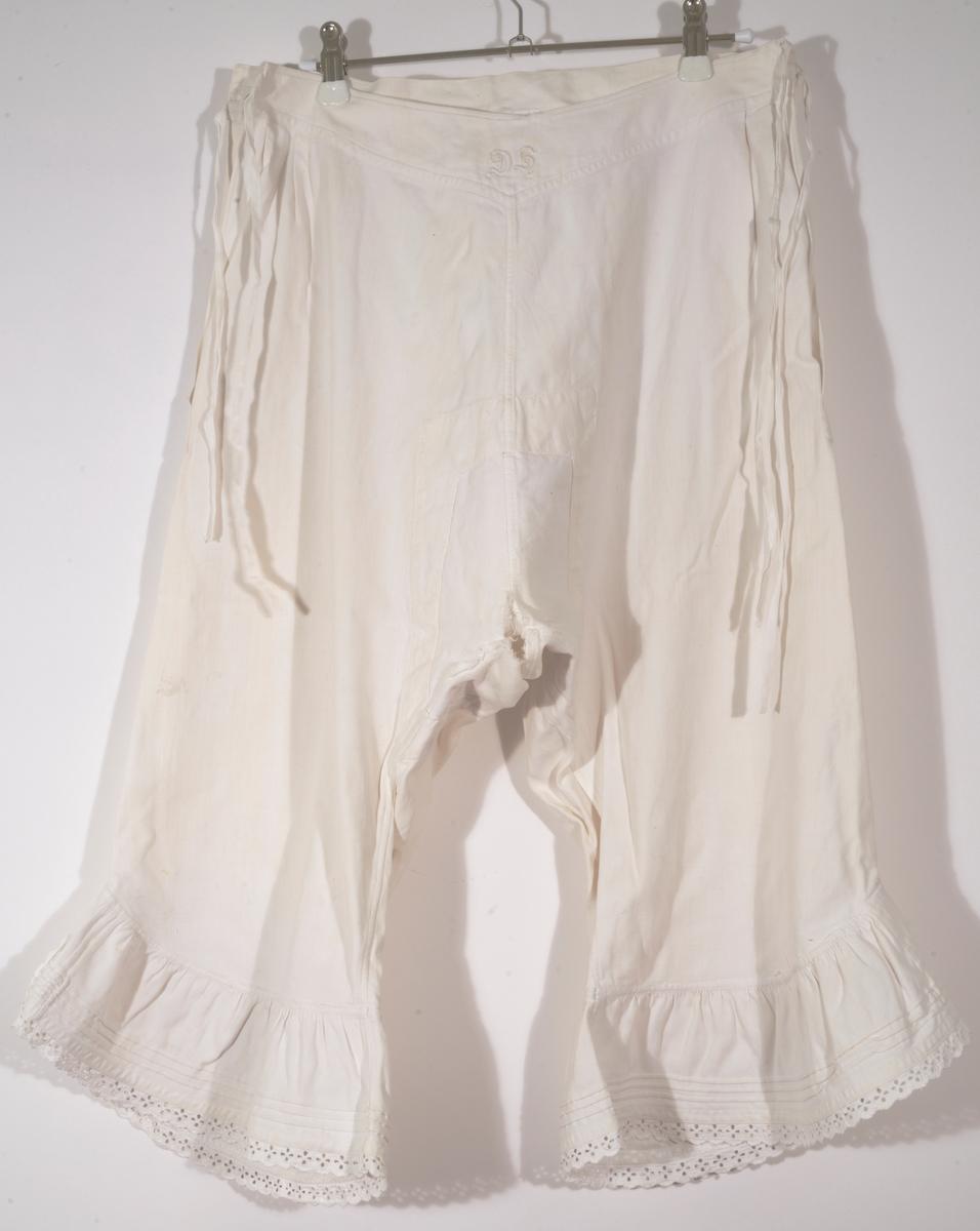Hvit underbukse av bomull med halvlange ben. Hjemmesydd. Rysjekant med biser og maskinsydd blonde nederst. Knyting på hver side av livet. Lukket i skrittet. Lappet og stoppet.  Monogram på fremside av linning, D (sikker), H (usikker)