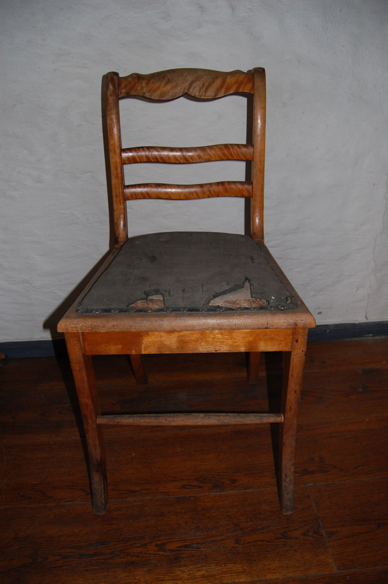Trestol med sete trukket i kunstskinn (?). Tre ryggsprosser, den øverste profilert. Likner AS.613-617, Biedermeier-stil. Rift i setetrekket.