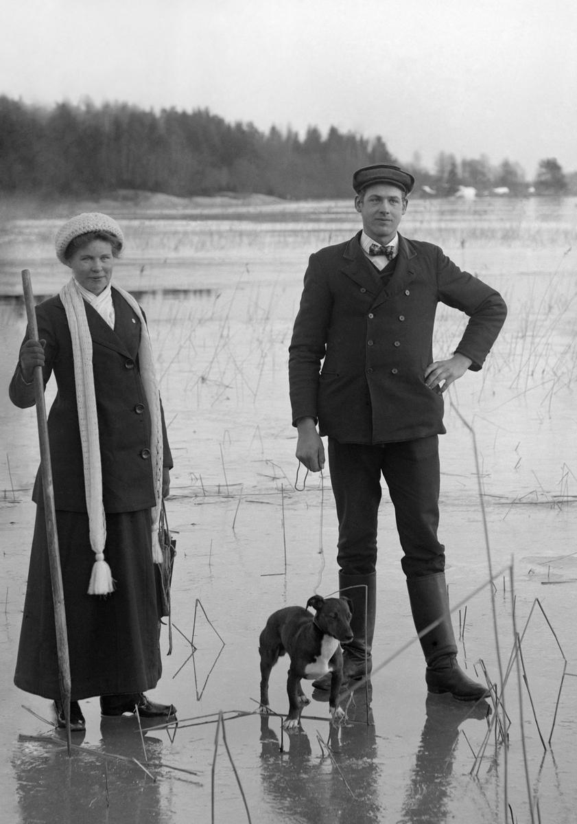 Syskonen Karlsson ute på hal is med hunden Chasse, rimligtvis i närheten av fotograf Emil Durlings hem Strömmen i Sankt Anna. I bild syns arrendator Karl Karlsson från Mossen på Norra Finnö och hans syster Ester Karlsson mer känd som Ester Bölja Bergström efter ett taget tillnamn och giftermål. Året är 1913.