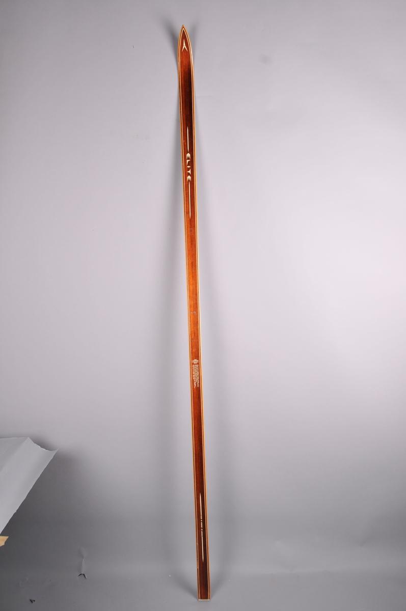 Langrennski laga av tre. Brunlakkera overflate, trekvite sidekantar.  Metallbeslag bakre tupp. Askjem-emblem på framtupp.  Noko innsving på midten.