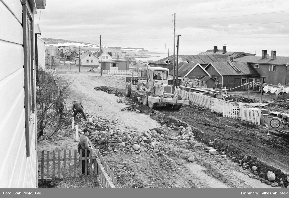 Vadsø 1969. Fotoserie av Ole Zahl Mölö. Veiarbeid og dosering av jord og stein med bulldoser. En mann i arbeid med stein og en gutt som står og bivåner arbeidet.