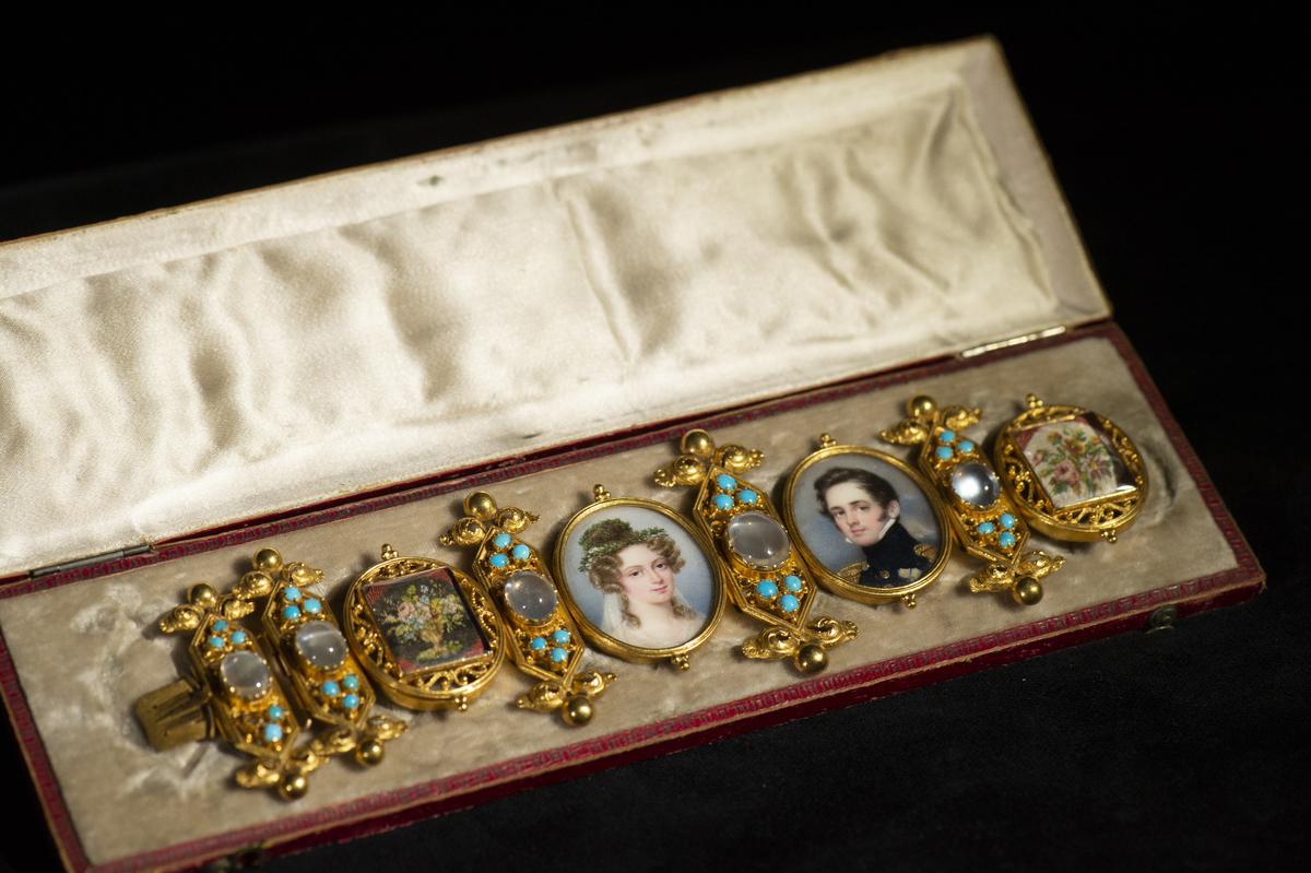 Bestående av 9 delar sammanlänkande med varandra. Fem delar består av rektanglar i guld med kortändarna spetsiga och med dekoration av guldknopp och guldblad. En av rektanglarna är något större än de andra fyra som är lika stora. På ovansidan av rektanglarna sitter på mitten en månsten samt tre små turkoser på vardera sida om denna. Mellan rektanglarna sitter fyra medaljonger. De två mittersta har handmålade porträtt. Det ena föreställer en ung kvinna med krona av blomster i håret samt en slöja som hänger ned från kronan på hennes axlar. Det andra porträttet föreställer en ung man i uniformsjacka. Paret är brukaren Barbara von Geymüller och hennes make, hovmarsalk Ulric Cronborg (1796-1844) . De gifte sig 1825 och armbandet är Bettys bröllopsarmband. De två andra medaljongerna består av mycket småskaligt handbroderi bakom en bricka av genomskinligt glas. Motiven föreställer två blombuketter med olika utseende på bakrund av vitt respektive svart. Anmärkning: * Material 3: Månsten, turkos. * Material 4: Glas. :2 Armbandsask av hård rödfärgad papp, bestående av en underdel och lock som öppnas och stängs med hjälp av gångjärn i metall. Bottens insida klädd med grå sammet. Lockets insida klädd med grått blankt tyg. Utsidan dekorerad med en guldfärgad bård. Asken kan stängas åt och låsas till med hjälp av två små metallkrokar som stoppas in i små metallmärlor. En krok är borta. Längd: 215 mm, bredd: 60 mm.