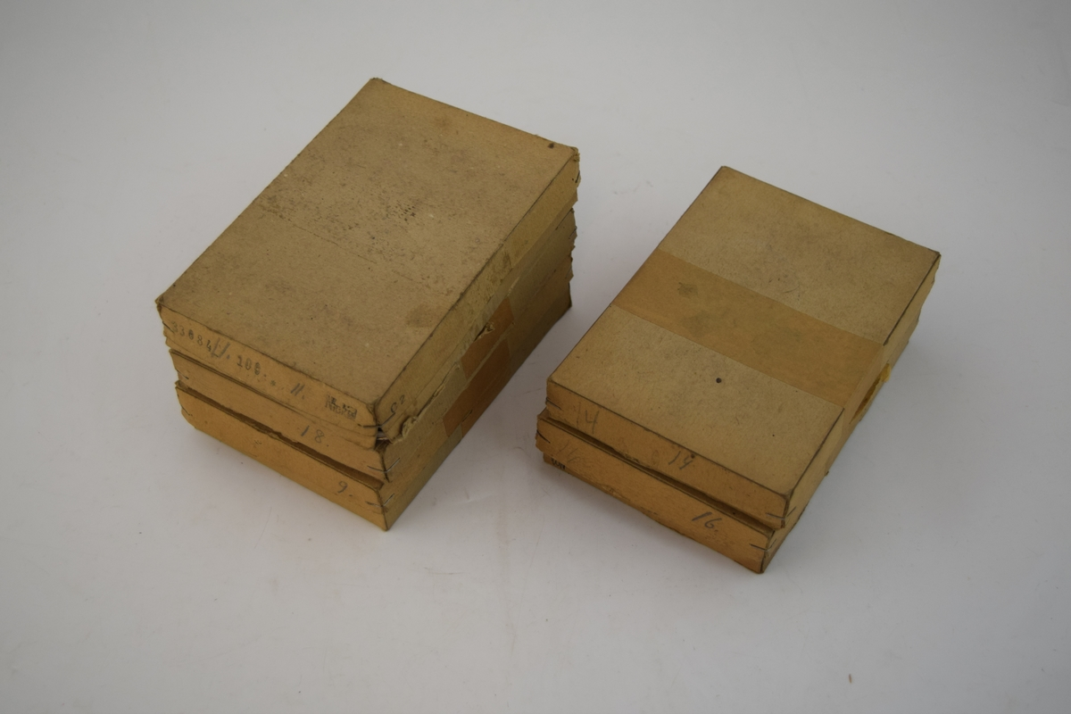 Fem stk. papiresker med bunn og lokk, inneholder stifter og spenner i ulike fasonger og størrelser til bruk på fottøy. Skillevegger i eskene skiller spenner og stifter fra hverandre.