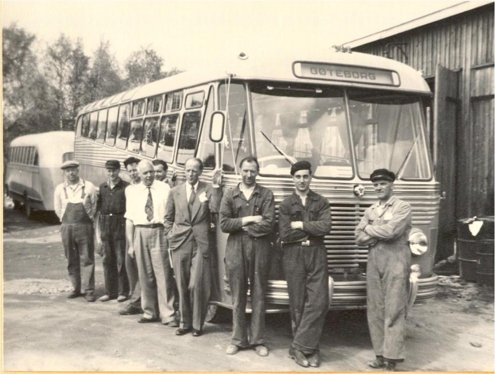 Personale ved NSB Hølandsrutene foran turistbuss utenfor verkstedet på Bjørkelangen