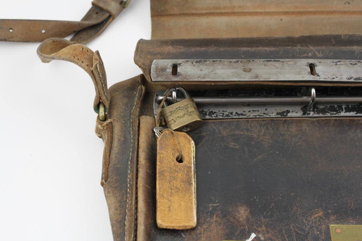 Lösväska i läder med klaff och två spännen. På framsidan en mässningsbricka med inskription i skrivstil. Väskan är försedd med låsten, hänglås och bärrem.