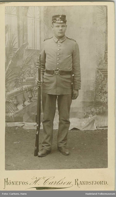 Portrett av mann i militæruniform og med gevær