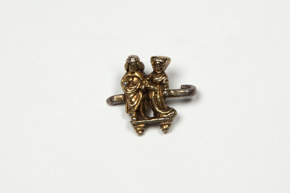 Fragment av spenne i forgylt sølv. Plastisk utformet kvinne- og mannsfigur i 1400-talls drakter. Figurene er flate på baksiden, stående på en liten plate. Loddet til kork, som er brutt i den ene enden.