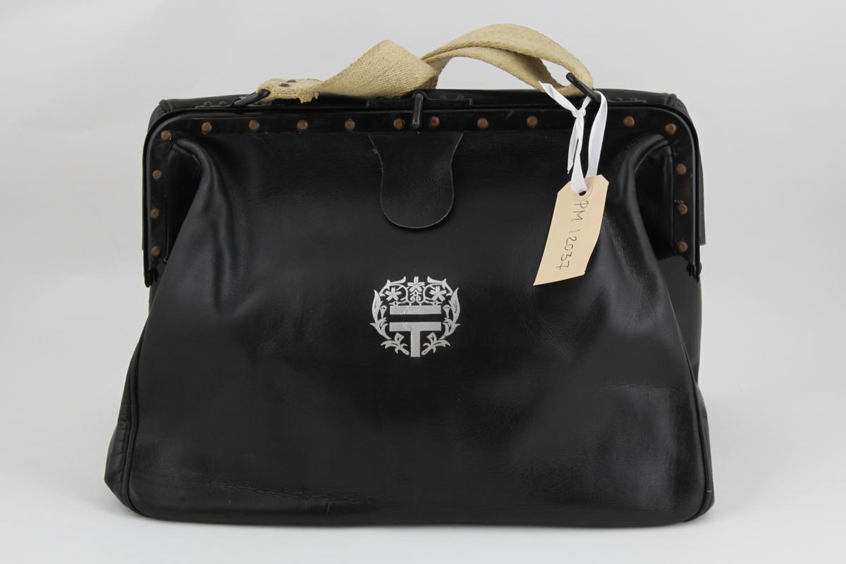"""Brevbärarväska av svart läder med bygel, tillslutningsanordning och axelrem, 4 cm bred av naturfärgad väv. På framsidan ett påtryckt """"silver"""" emblem och under bygelplösen en japansk inskription.  Ej använd."""