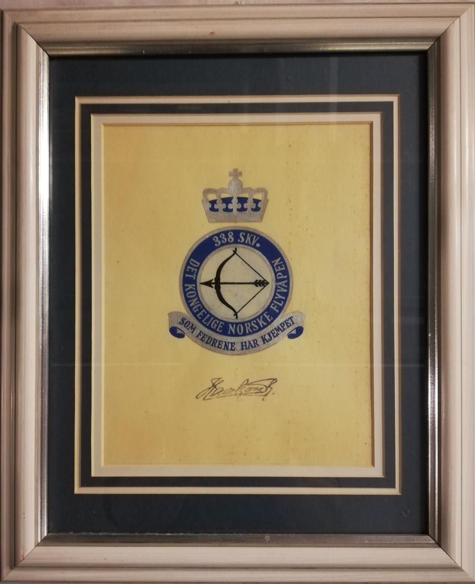 Skvadronens emblem i sølv og blått med en sort spent bue. Tekst rundt er: 338 skv Det Kongelige Norske Flyvåpen. Tekst under: Som fedrene har kjempet.  Signert av Kong Haakon 7.