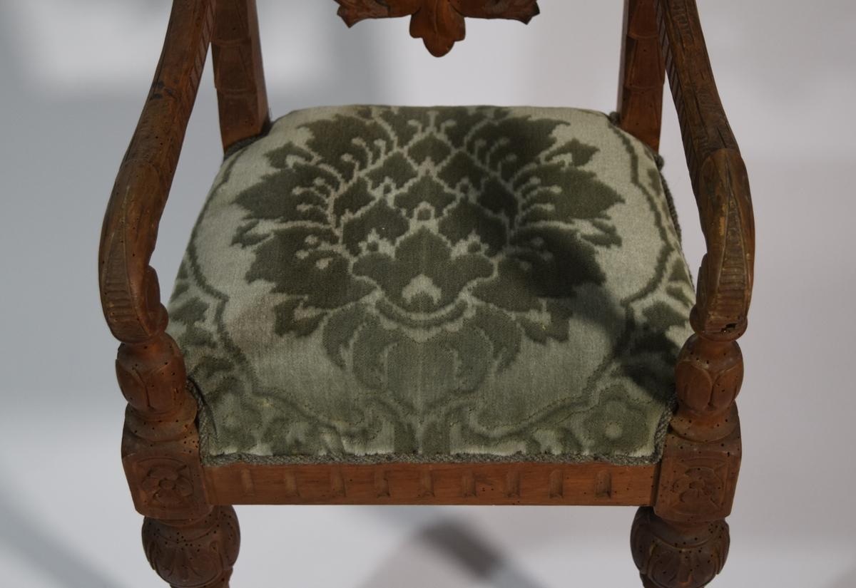 Stoppet sete med springfjærer og stoppet oval rygg, trukket med grønn plysj. Forben dreide, koniske, med riller og med kuleformet avslutning opp under sarg og kubisk form med dekor i sarghøyde. Bakben med enkelt, rektangulært tverrsnitt fortsettende i ryggstaver med dekor på forkant og avsluttet med utskåret, roselignende form i topp. Enkel sarg dekorert med loddrette skurd. Ryggfelt mellom ryggstaver består av ovalt stoppet midtfelt omgitt av skåret, gjennombrutt bladornamentikk avsluttet med vaseform over det stoppede felt, og herover utskåret eple og pærer. S-formede armlener avsluttet foran med dreiet forlengelse av forben.
