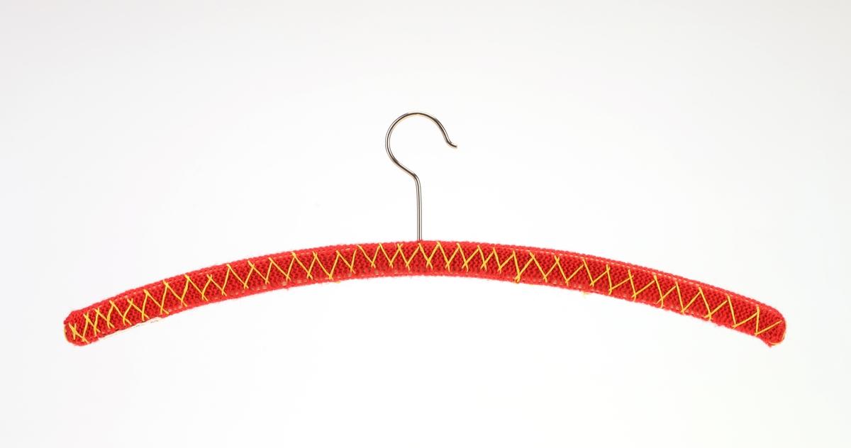 Tre enkle klesehengere laget av tre med strikket trekk. Trekkene er strikket i rettstrikk/rillestrikk. Det er strikket en hylse som er tredd på hengerne og sydd sammen i endene. Det er brodert på en enkel sikk-sakkbord på alle hengerne. Det er strikket i 3 ulike farger: grått, blått og rødt med broderi i henholdsvis rødt, grått og gult.  For oppheng er det en enkel krok i metall.