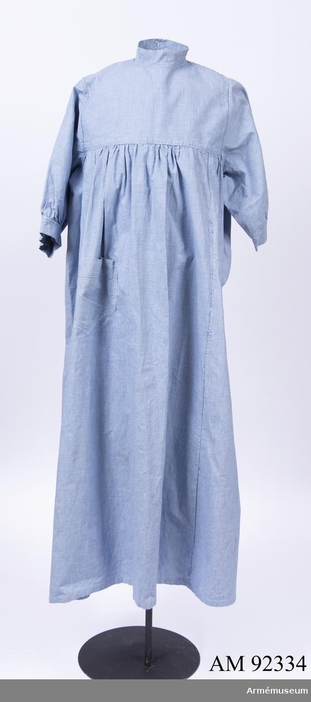 Förkläde tillverkat av blårutigt bomullstyg, knäppt i nacken.