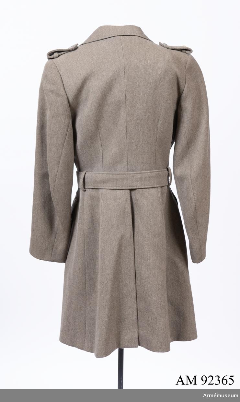 Jacka sydd i grå yllediagonal med märken och knappar för Svenska Blå Stjärnan. Till jackan hör ett skärp i samma tyg.