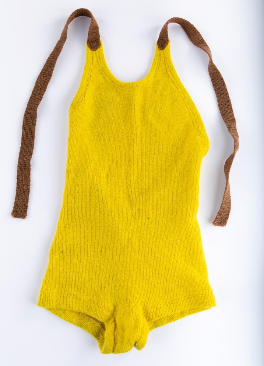 Hel ribbestrikket barnebadedrakt i ull, sennepsgul. Brune stropper festet foran, knyttes i nakken. Antakelig konfeksjon.