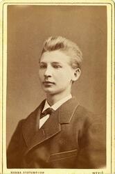 Porträttfoto av en ung man i kavaj och fluga.   Bröstbild, h