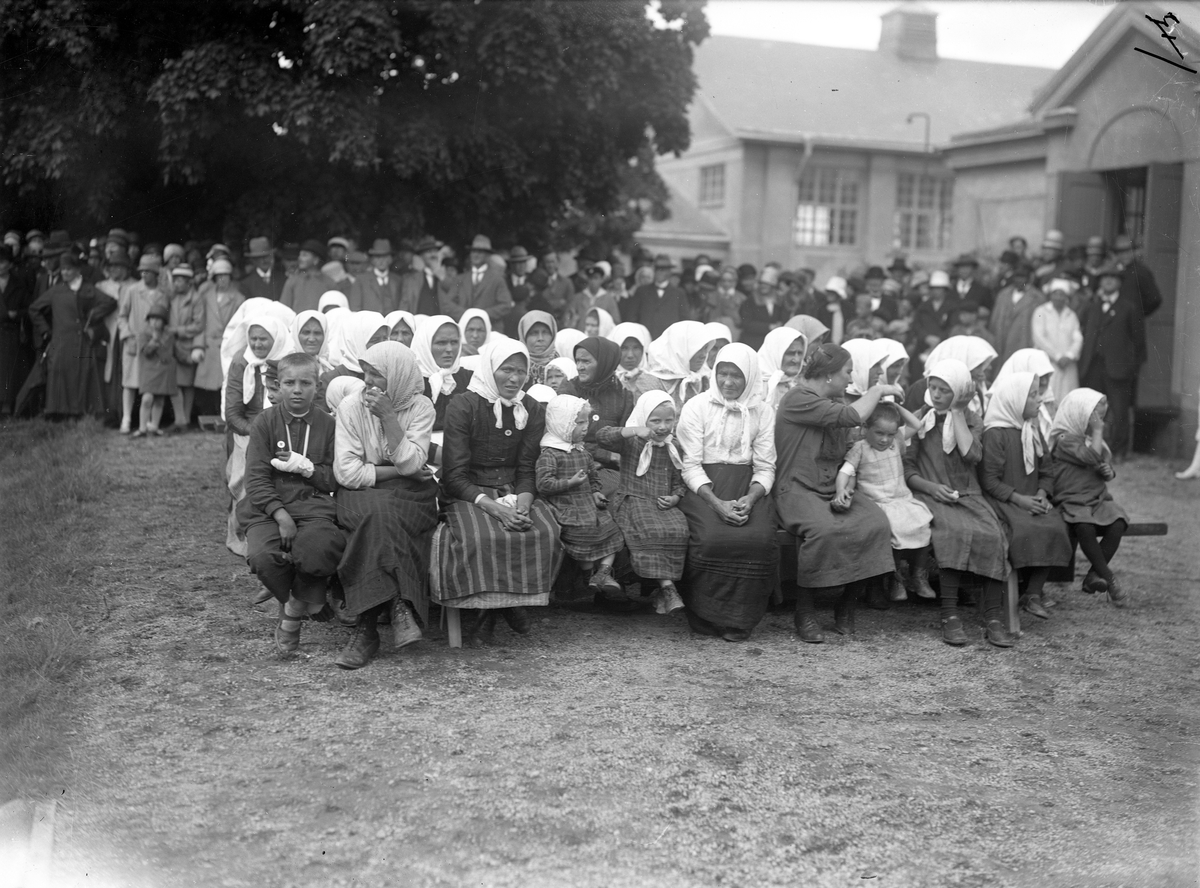 Svenskbybor på Ryhovs kasernområde i Jönköping 1929. Kvinnor och barn på bänkar vid lördagens gudstjänst med biskop Edgar Reuterskiöld. Pojken längst till vänster har fått bandage om några fingrar.