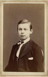 Porträttfoto av en ung man i mörk kavajkostym med väst och f