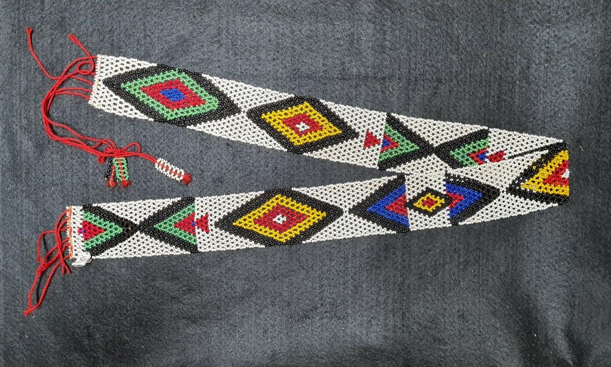 Ett av tre bälten av pärlarbete med geometriska mönster av olikfärgade pärlor.  22 448:1 L. 85 cm.  B. 4 cm.  22 448:2 L. 82,5 cm.  B. 4,5 cm.  22 448:3 L. 71 cm.  B. 4 cm.    Givaren, Stig Sundgren, föddes 1930 på den svenska missionsstationen Oscarsberg, vid Rorke´s Drift i KwaZulu-Natal, Sydafrika. Missionsstationen grundades av Otto Witt 1878. Stig Sundgrens far, Erik Sundgren (1900-1959) kom till KwaZulu-Natal 1928. Han träffade där sin blivande hustru, missionärsdottern Annalisa Fogelqvist (1907-1983). Annalisa hade kommit till Oscarsberg redan 1910 med sina föräldrar Sven och Ruth Fogelqvist. Annalisa som var uppväxt vid missionsstationen talade zulu lika väl som en infödd. Sven Fogelqvist, som var från Skara, arbetade för den svenska missionen i Sydafrika åren 1910 - 1928. Han återflyttade till Sverige på grund av dålig hälsa. Sven Fogelqvist blev efter hemkomsten domkyrkosyssloman i Skara och avled omkring 1931.  Erik Sundgren blev år 1948 den förste svenske biskopen i Sydafrika.  Familjen reste hem till Sverige 1935 och återvände till Sydafrika 1939. Stig Sundgren återvände för andra gången till Sverige 1945 och sattes i skola i Skara. Efter genomgånget läroverk och universitetsstudier i Uppsala prästvigdes Stig 1957. År 1958 fick han tjänst som präst i Borås. Åren 1960-1967 arbetade Stig Sundgren för Svenska Kyrkans mission i Rhodesia, nuvarande Zimbabwe. Hans huvudsakliga sysselsättning var då organisations- och utbildningsfrågor. Efter att ha återflyttat till Sverige har Sundgren varit bosatt och arbetat som präst i Brämhult, utanför Borås.'