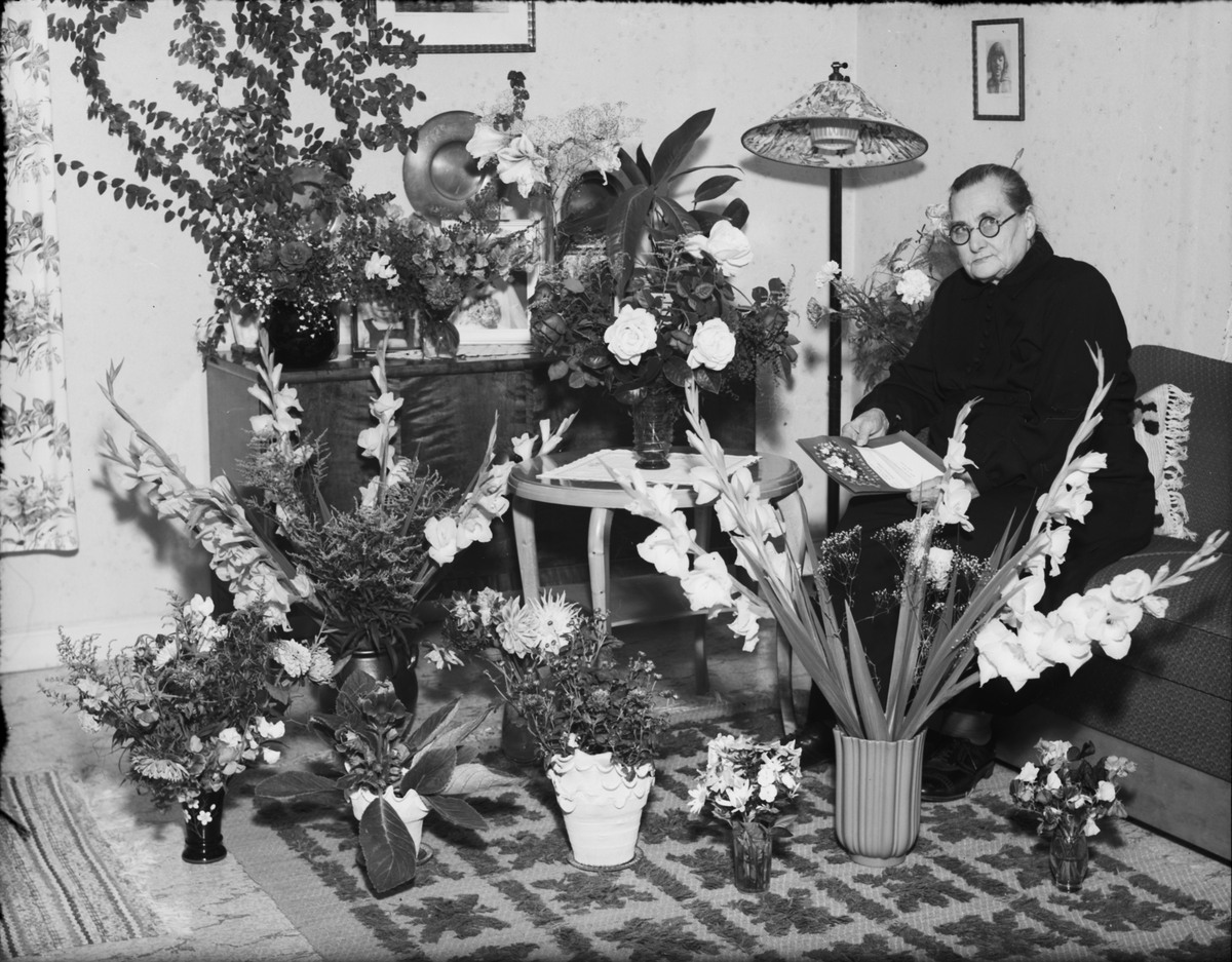 Kvinna i hemmiljö omgiven av blommor, Östhammar, Uppland