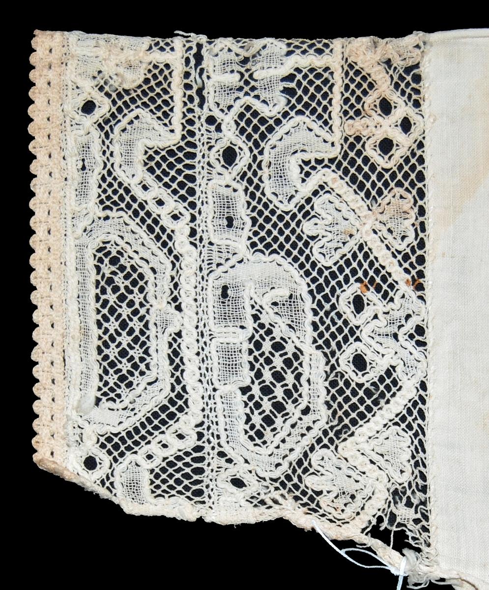 """Spets, sammanfogad av 2 st spetsar, dalknyppling, vit bomullstråd  med bomullsgrovände. kantad med vitt, maskintillverkat bomullsband. Spetsen fastsdydd mot vit bomullslärft, avklippt från hatt. Spetsen trasig i kanterna, lärften trasig. Pappersetikett med tryckt och med bläck och blyerts skriven text: Gestriklands hemslöjdsförening spettsutställning i Gävle 1916. Mockfjärdshatt. """"Klockros"""", """"Klockknytning"""", """"Vågen"""".  Pappersetikett med tryckt och med bläck skriven text: Gestriklands hemslöjdsförening spettsutställning i Gävle 1916. Mockfjärdshatt,"""
