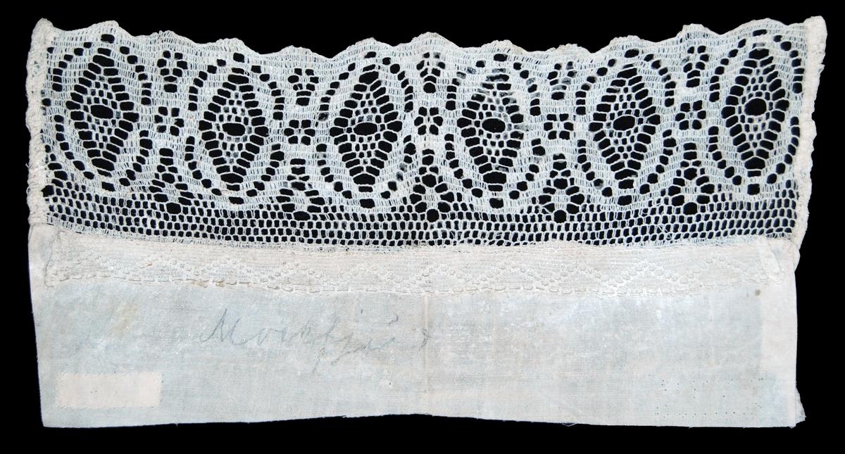 Spets, sammanfogad av 2 spetsar, den inre smalast samt sydd mot hattlärften, maskinvävd av vit bomullstråd. På lärften med blyerts skriven text: Mockfjärd.