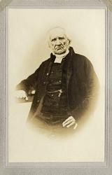 Foto av en äldre man i prästrock och prästkrage m.m. Han vil