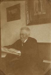 Foto av en äldre man med glasögon, klädd i bonjour med stärk