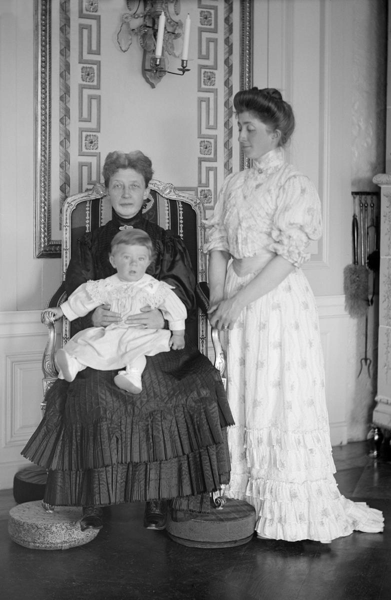 I den så kallade Kungastolen på Thorönsborgs gods sitter grevinnan Ebba Mörner med barnbarnet Carl Philip Bonde i knäet. Intill står pojkens mor Anna Bonde, född Mörner.