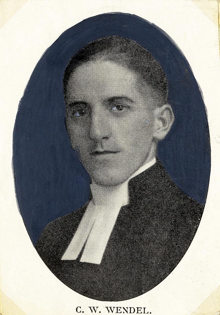 Foto av en man i prästrock och prästkrage.  Bröstbild, halvprofil. Ateljéfoto.