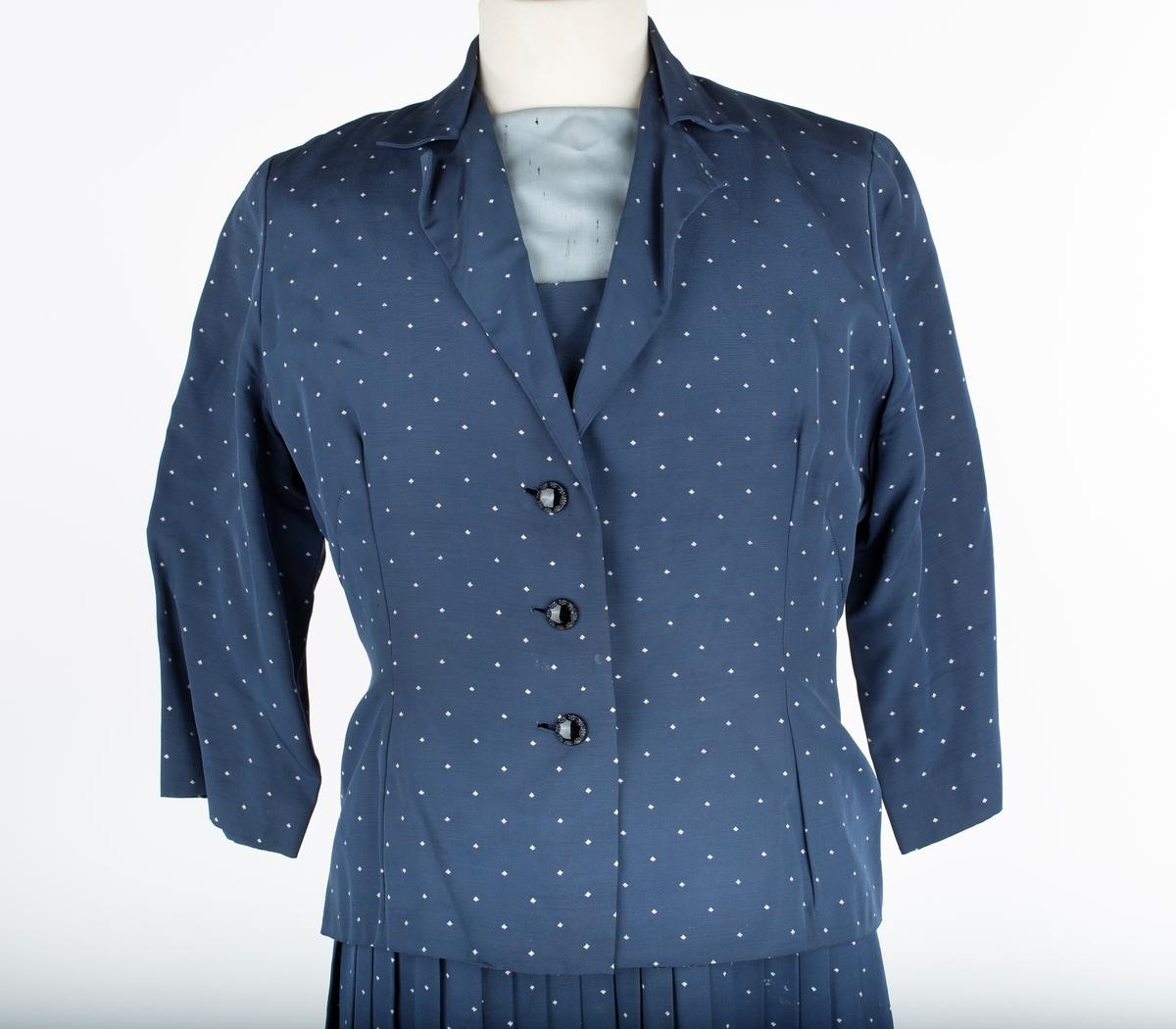 Kjole med jakke..  A: Kjole  Plissert skjørt, rette folder. Langt liv, firkantet halsskjæring, lengdesnitt forran og bak og skrå brystsnitt både over og under bysten. Belegg rundt hals og armrunging i lys grått spettet stoff. Glidelås (plast) i venstre side   Jakke er b) Innsvinget jakke, forknappet med 3 knapper, isydde 3/4 lange ermer, krage med slag, lengdesnitt og skrå brystsnitt foret med kremhvitt forstoff. Har 3/4 ermlengde  Brukt av Johanne Weydahl, Ø. Sundby gård i Nordby sogn, Ås kommune. Hun var mor til giver