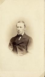Foto av en man klädd i kavajkostym med stärkkrage och fluga.