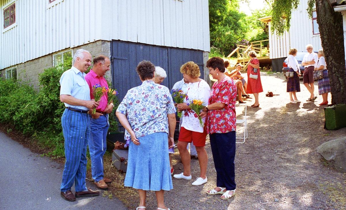Invigning av Ekebackens Hantverksgård (tidigare John Lindströms möbelsnickeri) på Gamla Riksvägen 81, början av 1990-talet. Gun Flygare från Vuxenskolan (i blå kjol) avtackar Köksorkestern med blommor. Till höger (i röd blus) står Asta Axelsson (Vommedal).