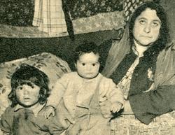 En kvinna och hennes två barn avbildade inuti sitt tält. Enl