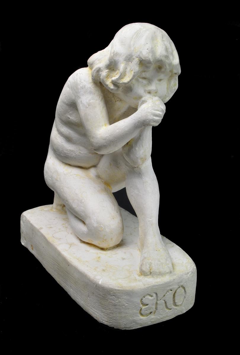 """Skulptur i gips av Edith Norée: """"Eko"""". Långhårig pojke sittande på huk med händerna framför munnen, formade för ljud. Rektangulär bottenplatta med inskription framtill: """"EKO"""". Signatur baktill: """"Paris Norée 1920""""."""