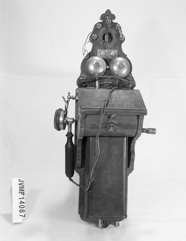 Väggtelefon av trä och metall med detaljer i bakelit. Tvår ingklockor upptill på framsidan. Hörlur i vänster sida. Tallur ser ut att fattas upptill.