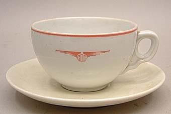 Kaffekopp från GDG av vitt porslin med röd dekor. Röd rand upptill och GDG:s logotyp på sidan, i form av deras initialer mellan ett par vingar.