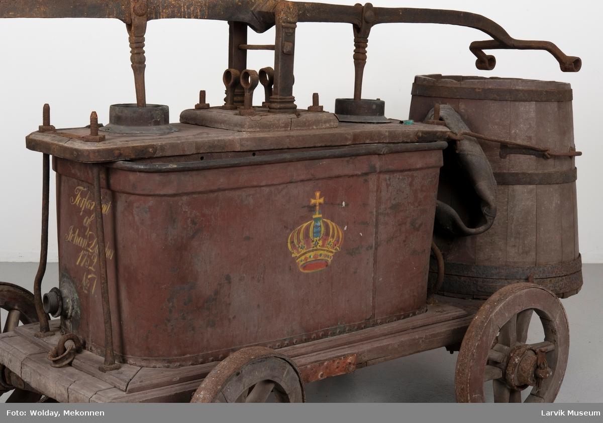 Brannvogn med vanntønne bak, lagget med jernband/håndtak festet med beslag/beholder av jernplate/pumpe- system av jern/festet til dragen av jern/2 hjul på hver side, av tre med jernbeslag over
