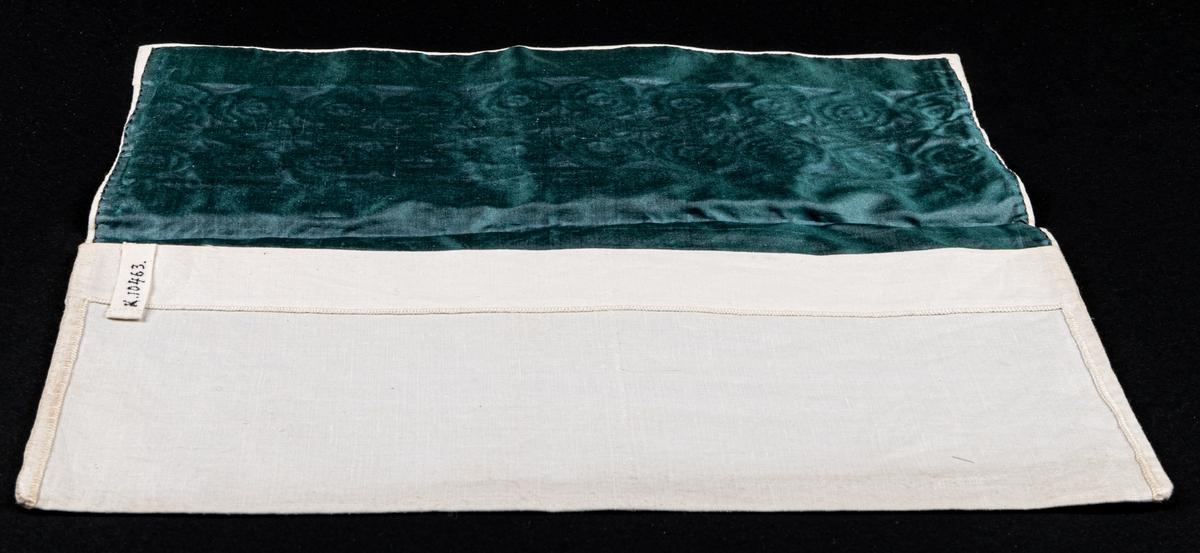 Servettväska i vitt linne med venetianskt broderi. Fodrad med grönt råsiden.