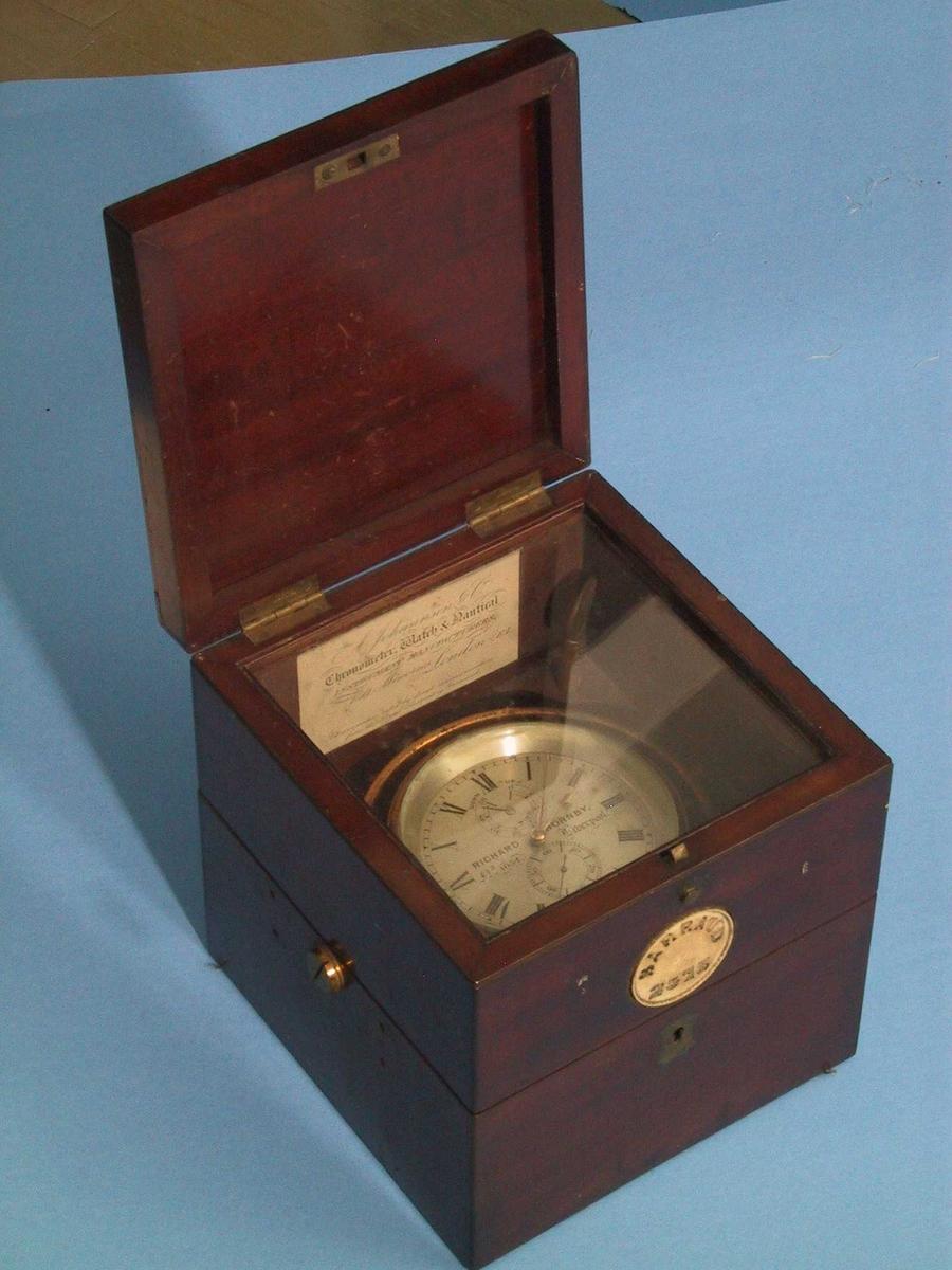 """a) Kronometer i kasse av   mahogni  med messing  beslag.   Metall  med messingbelegg,   glass.   a)H.18.Bunn 17,1x17,5. Diam.kron.10,7. b)H.24,4.Bunn L.31,2.  B.24,4.  b) Ytre kasse,   palisander  med stopning innv.av puter trukket med seilduk og seilduksgarn. a) Firkantet kasse med to lokk, det øverste er smalt, under dette en  glasskive gjennom hvilken en kan se kronometret. Det annet lokk deler  etuiet i to. Kronometer i metallring, alt med messingbelegg, som  dels flasser av, firmanavn på skiven har romertall:   Tilst. Febr. 1967: metallet litt anløpet, ellers god  b) Firkantet kasse med lokk som deler kasse i to, messingkrok. På  sidene et lite buet felt i bunnen med hull for skrue. Midt i sidene  festet en rem, som festet over lokket. Innvendig puter i bunn og  side. Flg. papirer lå i bunnen:  1) Kvittering for kjøpet, datert August 8th 1923. har ikke pris =  garantiseddel.  2) Firmakort fra """"Alf. Willings & Co. Marine Opticians and Compass  Adjusters.73, Church Street, West Hartlepool . Authorized Compass  Adjusters for Norwegian Vessels at this Port by Appointment of the  Norwegian Government.""""  3) En pappskive med blå blyant. ORA.  4) Papir med avlest kronometer for juni, juli og aug. 1935. øverst:  Kronometer no. 1054 """"Ora"""".  5) Ditto for 9. febr. 1926. o.a. datoer i febr.  6) Ditto for 15/9."""