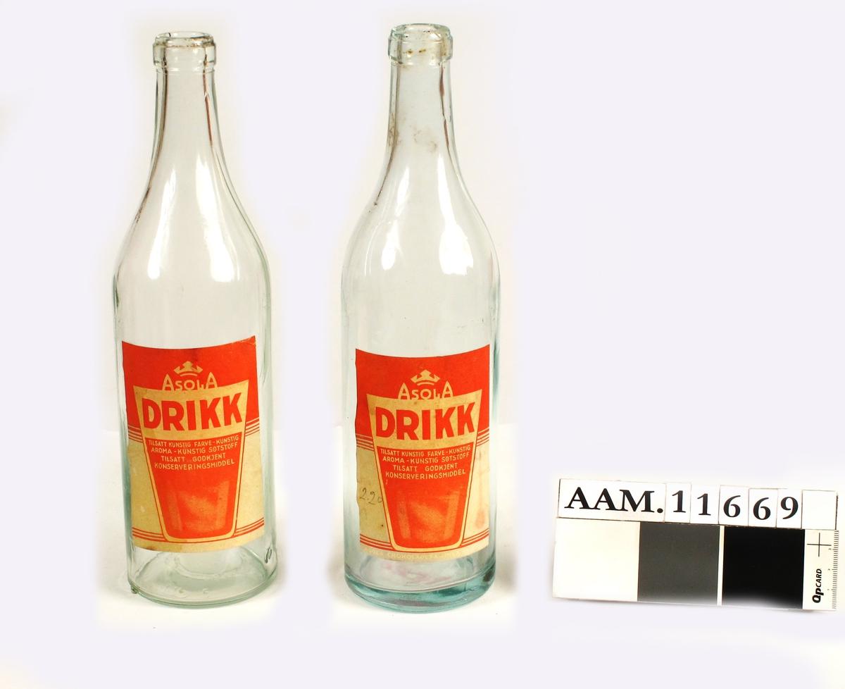 Flaske for leskedrikk  fra slutten av krigen 1940 45.   To helflasker med kirsebærrød saft, tekst på rød og  hvit etikett:   Asola Drikk. Tilsatt kunstig farve km,   kunstig aroma kunstig søtstoff ±ilsatt   godkjent konserveringsmiddel.   Tilstand: god.