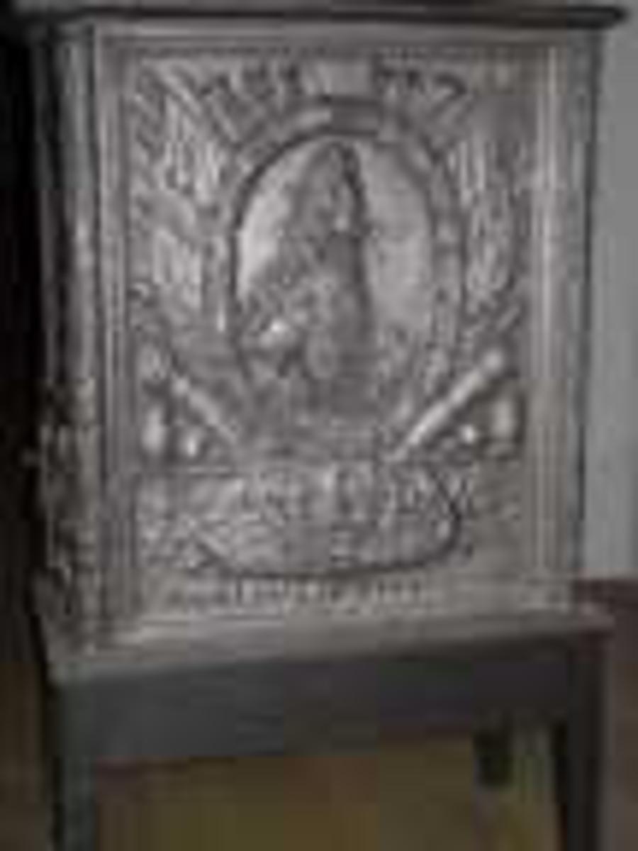 Langsiden med  Frederik 4s brystbilde i profil mot h. i oval laurbærmedaljong, omgitt av krigerske emblemer. Derunder laurbærgrener hvorpå skjold med den norske løve.