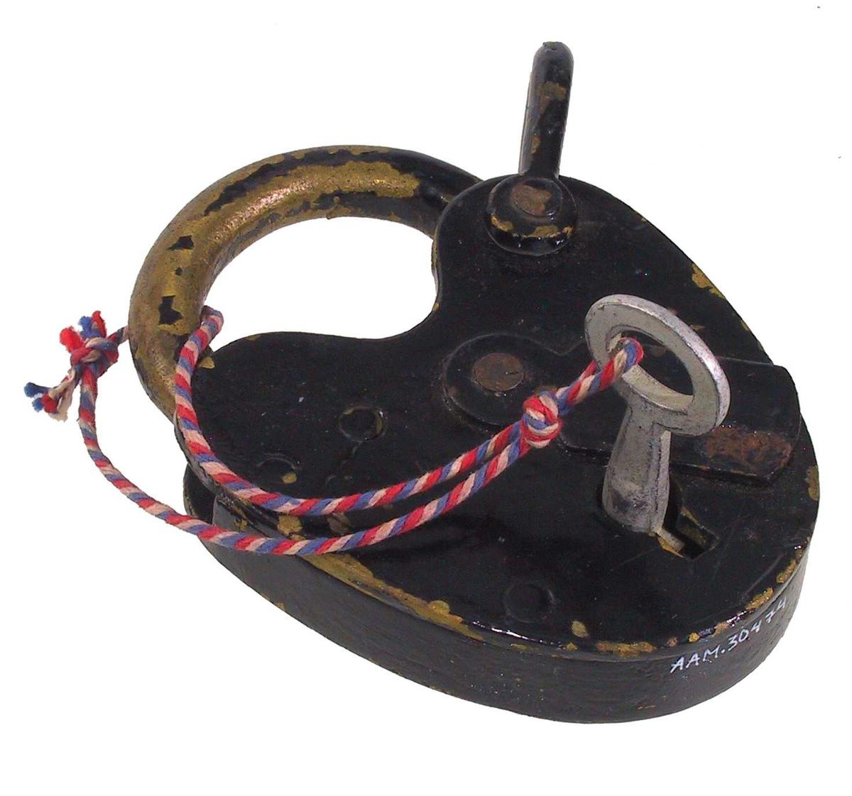 Form: Stor hengelås, nesten hjerteformet. Nøkkel festet til låsen med snor.