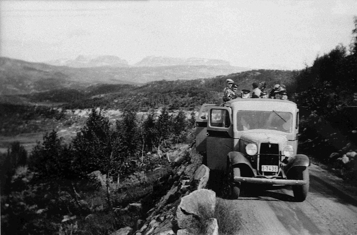 """Busstur. Bussen er en Ford V8 1933-34-modell. Den ser ut til å ha reg.nr. I-7436. Høyeste nr. i Norges Bilbok 1935 (utkom på vårparten 35?) var I-7403. Legg merke til  åpen bakdør, og at taktrekket er rullet tilbake (""""solskinnsbuss"""")."""