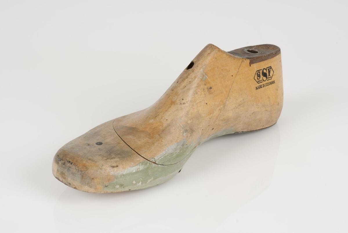 En tremodell i to deler; lest og opplest/overlest (kile). Høyrefot i skostørrelse 42, og 8 cm i vidde. Hælestykket i metall.