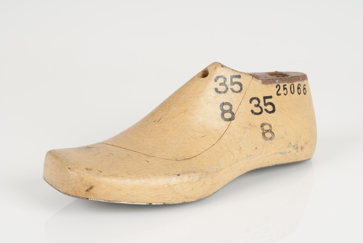 En tremodell i to deler; lest og opplest/overlest (kile). Høyrefot i skostørrelse 35, og 8 cm i vidde. Lestekam i skinn. Såle i metall.