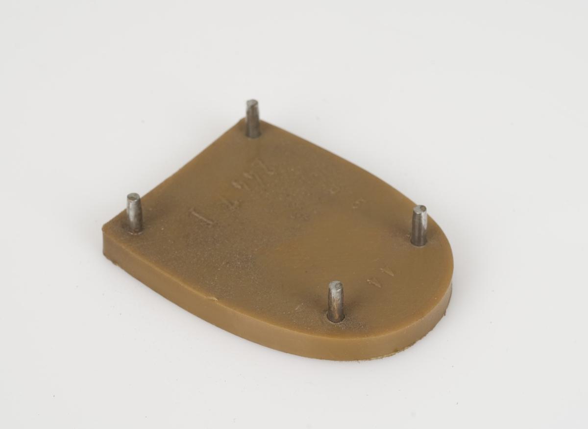 En hælflikk av plast. Fargen på hælflikken er lys brun. Fire skruer festet på hælflikken.