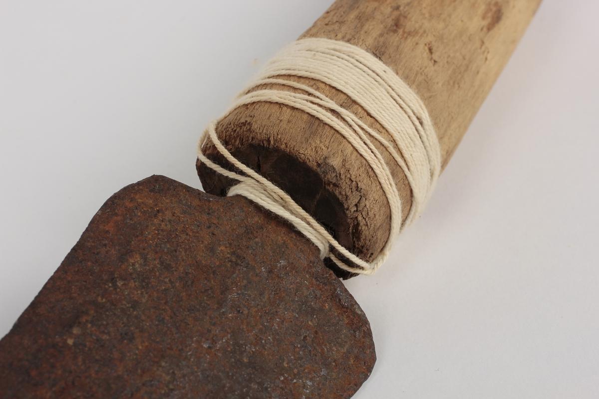 Redskap som brukes for å fjerne bark på hogst. To skaft med skjærebladet mellom. En hvit hyssing/ tråd er surret rundt det ene skaftet.
