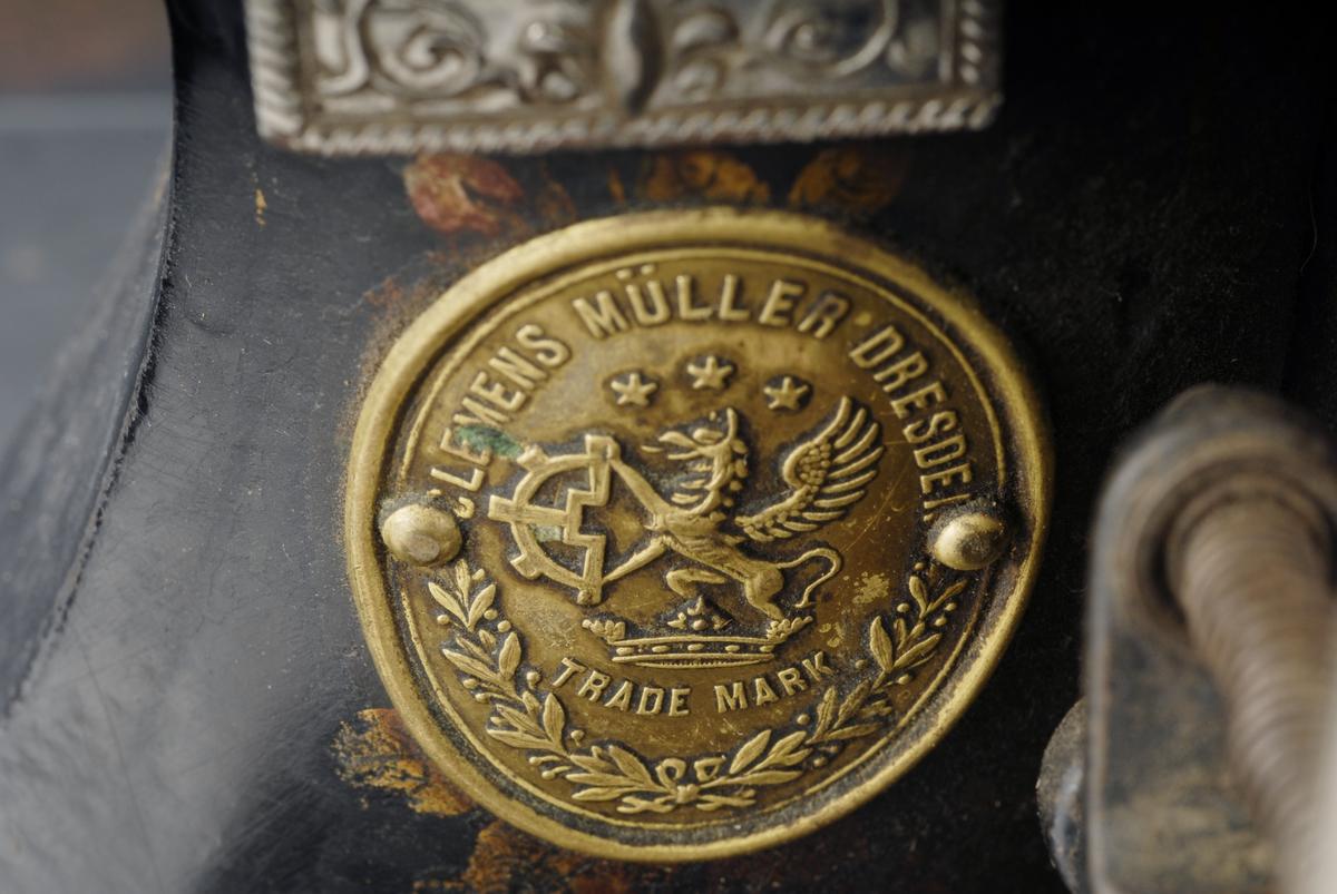 A: Symaskin. B: Spolehus med spoleinnlegg, sort tråd. C: Spolehus med spoleinnlegg,  sort tråd.   Symaskin av jern på en treplate. Sveivknapp i porselen. Hulrommet under maskinen inneholder en løs blikkplate, to trådspoler (B og C) og en knapp. To stoffbiter ligger på sybrettet.